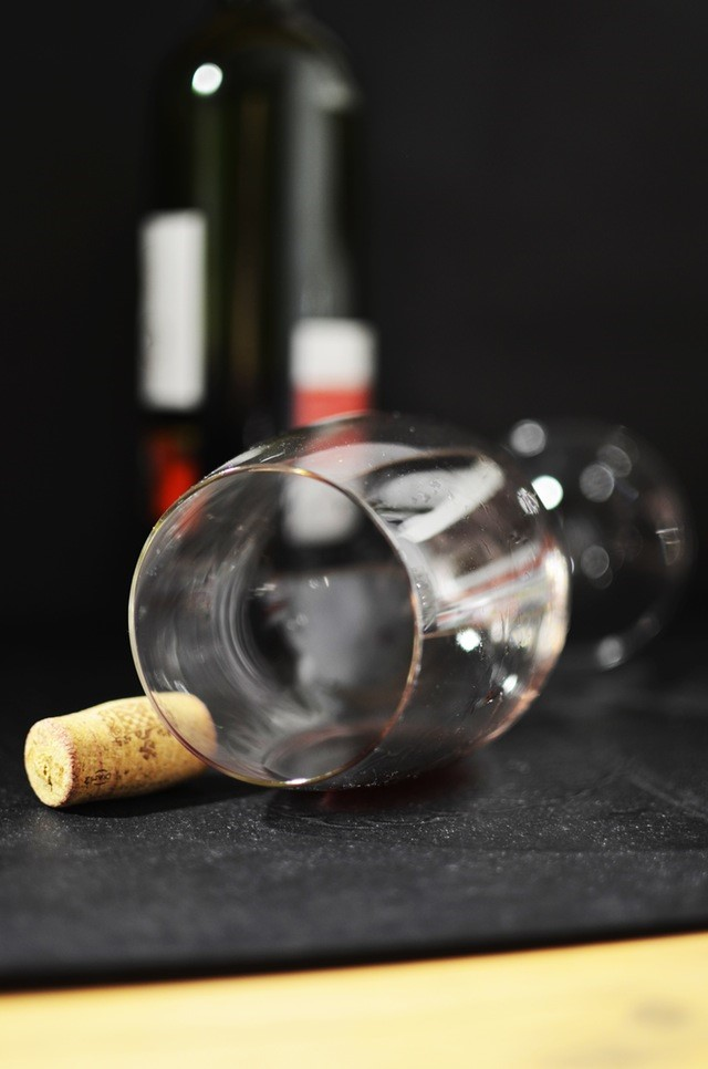 Et vinglas foran en flaske vin.